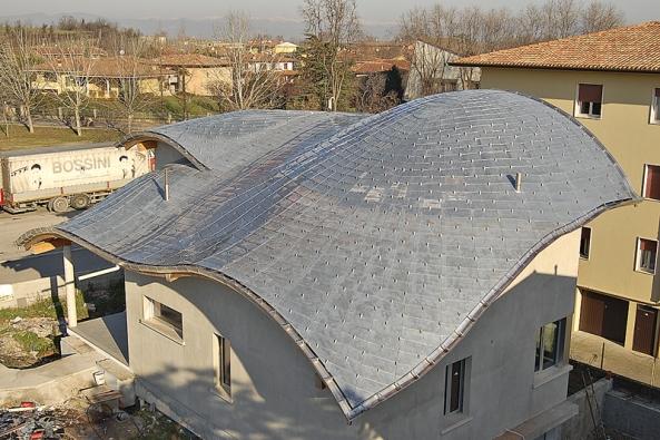 Zajímavý tvar střechy pokrytý asfaltovými šindelemi svrstvou mědi na povrchu (TEGOLA).