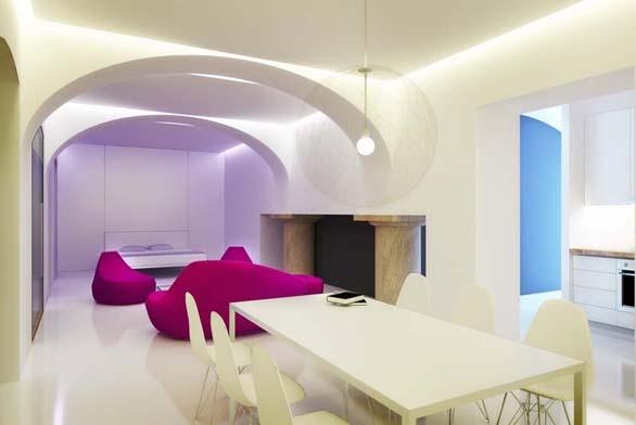 Obytná síň je jídelnou, obývacím pokojem a ložnicí vjednom. Vbílém interiéru nechali architekti vyznít původní pískovcové sloupy a doplnili je červeným barevným akcentem – sezením.