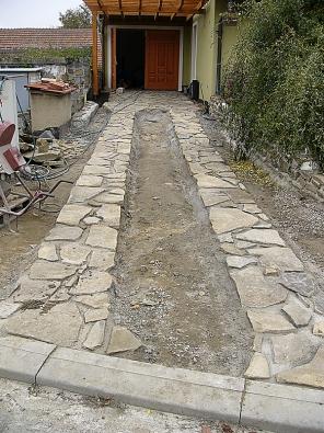 Momentka zvýstavby příjezdové cesty ke garáži. Zpevnění je realizováno štípaným kamenem.