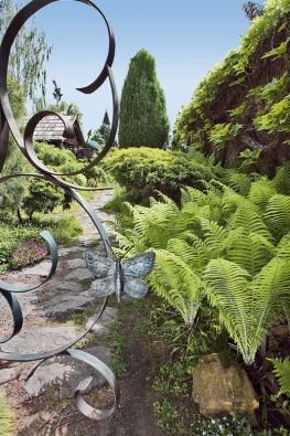 """Kovaná brána nás uvádí do zahrady patřičně """"umělecky""""."""
