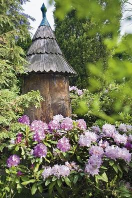 Starodávný úl zjednoho kusu dřeva objímají rozkvetlé rododendrony.