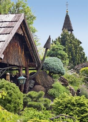 Ze zadního cípu zahrady vykukuje štíhlá vysoká zvonice.