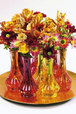 Bohaté slavnostní aranžmá představuje téměř baletní seskupení pestrých váz na zlaceném podnosu. Dojem skupiny baletek se zdviženými pažemi vytvářejí květiny odlišných délek. Různé odrůdy chryzantém doprovázejí růže, Anigozanthos aHypericum. Rychlé na přípravu, vhodné především jako ozdoba na konferenční stolek.