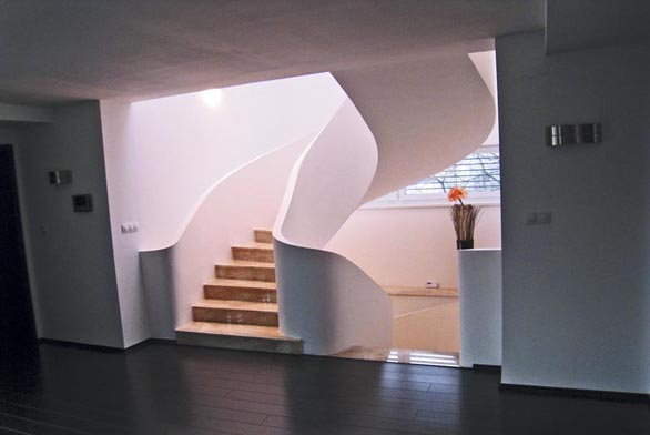 Až nadpozemská atmosféra na nás dýchne při pohledu na toto schodiště. Čím to je? Mnoha kontrasty dosaženými hrou světel a stínů. Kontrast tmavé podlahy haly s dobře prosvětleným schodišťovým prostorem, kontrast bílé barvy schodiště a okolních stěn, krémový nádech italského mramoru a také půdorysný tvar podkovy postavený schodištěm do prostoru. Již brzy bude schodiště doplněno o nerezové madlo, které zkopíruje křivky schodiště. Schodiště oválných křivek ve čtvercovém půdorysu je samonosné, kotvené pouze do hran spojovaných stropů.