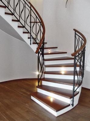 Jednoduchý tvar J v koutu prostorné haly rodinného domu. Stupnice z dřevěného masivu s propracovanými detaily v zatočení. Kované zábradlí s dřevěným madlem lichoběžníkového profilu působí velice stabilně, bezpečně a komfortně. Schodiště osvětlují svítidla v podstupnicích. Bílá barva podstupnic a zakřivené spodní části nosné desky konstrukci opticky odlehčují.