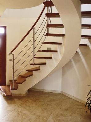 Železobetonová konstrukce umí vyhovět také požadavku na vzdušné schodiště. Například pomocí po kručnici stočené střední schodnice, do které jsou pomocí nerezových ploten připevněny dřevěné stupnice. Nerezové zábradlí je na vnitřní straně kotveno do dřevěných stupnic a zakončeno stejně stočeným dřevěným madlem. Mořené stupně, madlo a nerez zábradlí pak jemně vystupují z bílých ploch stěn a schodnicového samonosného nosníku.