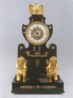 Portálové empírové hodiny, první čtvrtina 19. století, na černém obdélníkovém soklu z černého leštěného dřeva dva titáni nesoucí portál, apliky tlačená mosaz, výška 65 cm.