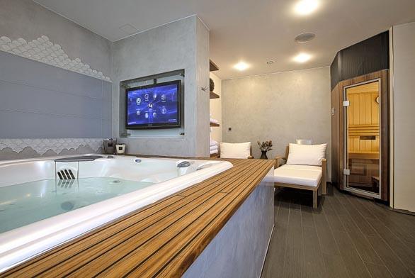 Jedna z koupelny slouží jako domácí lázně - masážní vana Persea (USSPA) pro 5 osob, sauna (Villeroy & Boch) a všudypřítomné televizní obrazovky.