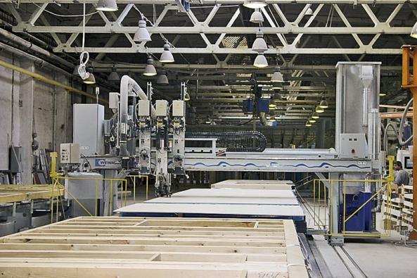 Takto se v továrních halách vyrábí dílčí stavební prkvy budoucích domů. Na počátku linky postupně vznikají rámy, na konci z pásů sjíždějí hotové sendvičové konstrukce obvodového pláště a vnitřních příček.