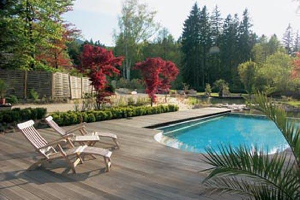 Kolem bazénu je dřevěná terasa