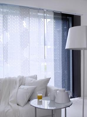 Tenký, lehký a světlopropouštějící závěs Anno Ljuv je ukotven nahoře i dole v kolejničkách za pomoci systému Kvartal (IKEA).