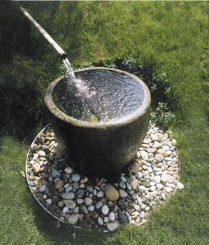 Zahradní kašnu s kamennou nádobou zdobí modrofialové kvítky barvínku.