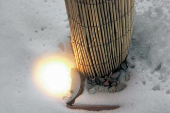 Světlo ze zapuštěného svítidla se dere skrz sníh.
