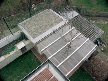 Zahradní domek se zasklenou pergolou a paulovnií.