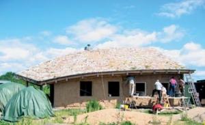 Dřevostavba domu s roubenou konstrukcí a hliněnými vyzdívkami a omítkami.