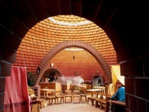 Pohled do interiéru Waldorfské mateřské školky v německém Sorsumu, jejíž klenby jsou postaveny z nepálených cihel. Klenební pasy nad průchody jsou ze statických důvodů z cihel pálených. Princip klenby je u stavby tohoto typu velmi vhodný. ´Vytváří pocit jistoty a archetyp mateřského lůna či jeskyně. Členitý povrch stropů zlepšuje akustiku a zpříjemňuje kvalitu estetického vnímání prostoru.