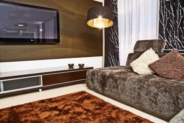 Na stěnu v obývacím pokoji použila designérka teplou temně hnědou barvu, aby LCD televizor příliš nevyčníval do prostoru a pocit pohledu na stěnu působil příjemně.
