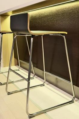 Barová židle z masivu a kovovou podnoží o výšce 63 cm slouží pro posezení u protažené pracovní desky o výšce 90 cm.