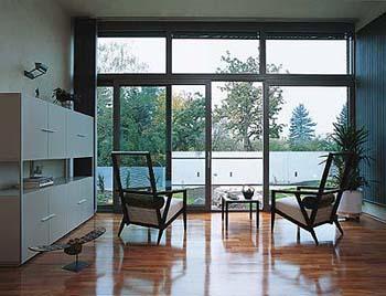 Společenská část se sezením má nejtěsnější kontakt se zahradou přes celoprosklenou stěnu, která je doplněna ještě výhledem na jih skrze horizontální špaletové okno.