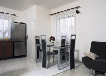 Jídelní zákoutí s tvarově jednoduchým nábytkem.
