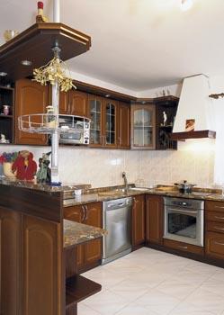 Poněkud rustikální ráz kuchyně vyvažuje úsporný design obývacího pokoje.