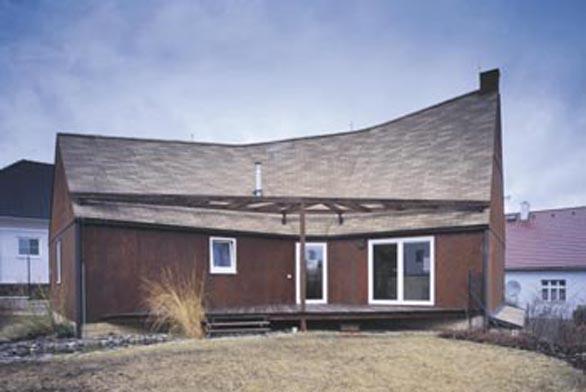 Hřbet střechy se svažuje od západního průčelí s krbovým komínem.