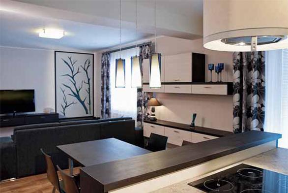 Tím, že designérka navrhla nábytek na míru, se naskytla příležitost využít mobilního posunu jídelního stolu, který buď navazuje přímo na kuchyň, nebo se přesune k vytvořenému příborníku zavěšenému na stěně.