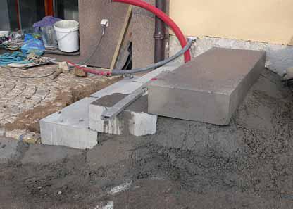 Na tomto obrázku je zřejmý způsob pokládky monolitických schodů i kamenné dlažby. Betonová patka samozřejmě zmizí pod zemí. Schody se staví odspodu na zhutněný štěrkový základ a polosuchý beton. Přední hrana je kvůli odtoku vody a komfortu chůze o cca 0,5–1 cm níže.