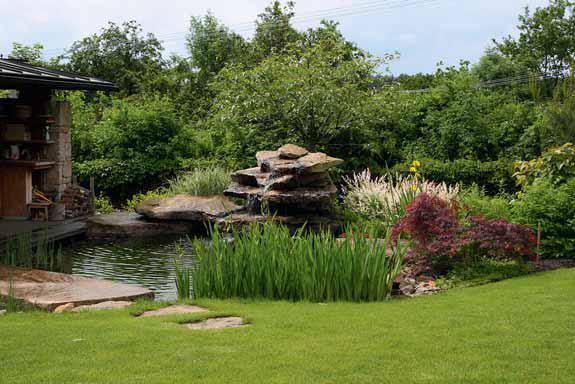 Jezírko s kamennou kaskádou navazuje přímo na terasu altánu. Bujná zelená clona chrání soukromí a zahradu opticky propojuje s okolními starými zahradami.