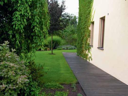 Vstupní partie zahrady je s velkou obytnou plochou propojena dřevěným chodníkem.