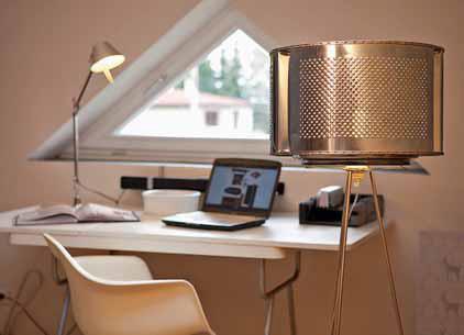 Perforovaný plech se opakuje i na stojací lampě, jejíž stínidlo je ze staré pračky. Stolní lampu TOLOMEO MINI vyrábí ARTEMIDE.