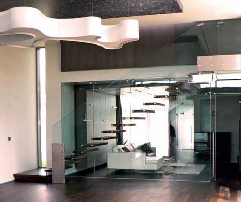 Přímé schodiště (design Titz a Augustinová) je tvořeno dřevěnými nášlapy z šedého dubu nesenými skleněnými bočnicemi ve funkci zábradlí a dělicí stěny, cena k doptání u prodejce (QL INTERIER).