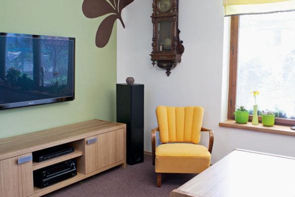 Čelní stěna dostala nový nátěr v barvě zelených oliv. Nepřehlédnutelnou dekoraci tvoří krásné starožitné hodiny po babičce a obrazy, ke kterým se vážou vzpomínky celé rodiny. Plazmová televize byla velkým přáním tatínka paní Radky, jejím umístěním se tradiční styl smísil se stylem zcela moderním.