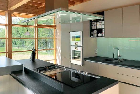 Odsavač Sombra 68 l A (GAGGENAU) má spodní sklo na zakázku dodané ve zcela shodné zelenkavé barvě, která je použita na obkladu stěny za pracovní deskou.