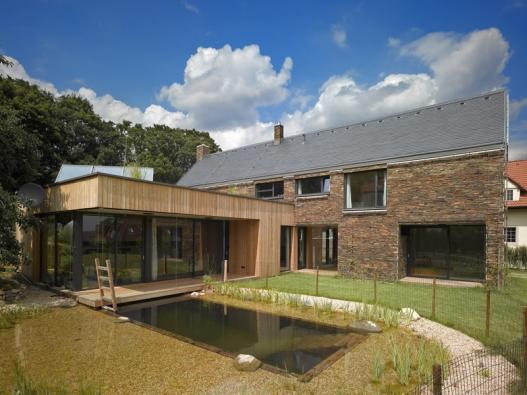 Základní jednopodlažní hmota domu spodkrovím se sedlovou střechou je vzadní části protknuta přízemní hmotou obývacího pokoje splochou zelenou střechou.