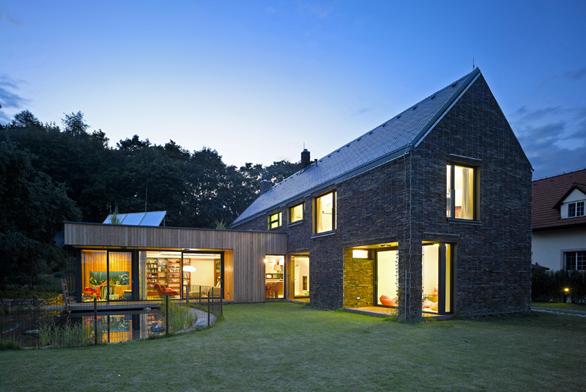 Budova garážového stání sdílnou tvoří předěl mezi pobytovou zahradou apřístupovou cestou kdomu.