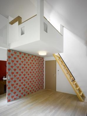 Nadčasově aúčelně řešené vnitřní dispozice obytného prostoru. Dřevěné schodiště vede na zavěšenou podestu, za stěnou se nachází koupelna.