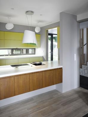 """Pohled do kuchyně spracovním """"ostrůvkem"""".  Přízemní části dominuje velkorysý obytný prostor, dělený na jídelní aobývací část."""