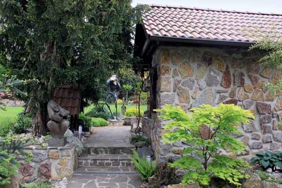 Schodiště k letní kuchyni lemované zelení a sochami.