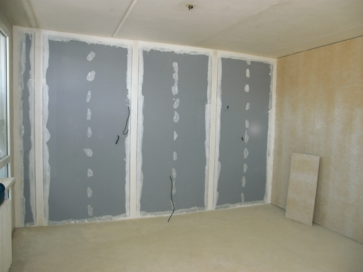 Vytmelená sádrokartonová předstěna zmodrých akustických desek Rigips. Předsazené stěny zaberou jen 6,5 cm při jednoduchém a 8 cm při dvojitém opláštění akustickými deskami. Přidají 9 -12 dB (decibelů) akustické pohody. Problém shlukem ze sousedního pokoje je vyřešen.