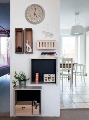 Zeď mezi vstupem do ložnice a do kuchyně je místem, které při příchodu domů nemůže nikdo minout. Proto tu jsou hodiny a police vyrobené ze starých šuplíků a šuplíčků, kam se dává došlá pošta, rozečtené knížky a účtenky určené k archivaci.