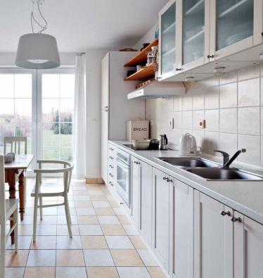 Bílá neutrální kuchyň z IKEA je doplněná bazarovým nábytkem a otevřenými policemi, na nichž je k dispozici všechno potřebné.