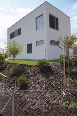 Střízlivý tvar a šedobílé fasády reprezentují nadčasovou architekturu, která bude dobře vypadat jak v sousedství s přírodou, tak i s různorodou zástavbou, která v okolí zřejmě časem vznikne.