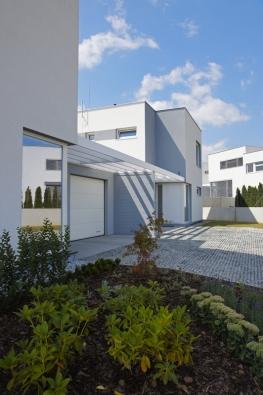 Jednotlivé domy jsou od sebe odděleny garážemi. Vjezdová vrata a prosklené rohové zádveří kryje slunolam z lepených dřevěných hranolů.