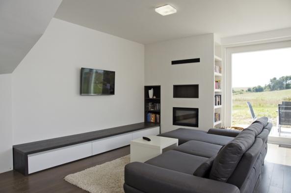 Podlaha z mořeného dubu dodává interiéru příjemný zemitý charakter. Obývací pokoj zdobí atypická rohová knihovna s integrovaným krbem.