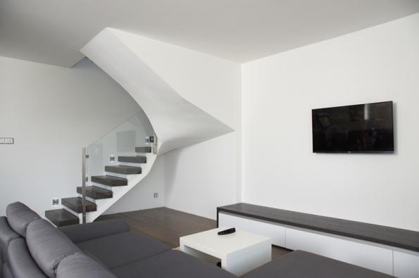 Lomená železobetonová schodišťová deska s masivními dubovými stupni a skleněným zábradlím poutá pozornost jako zajímavá dominanta interiéru.