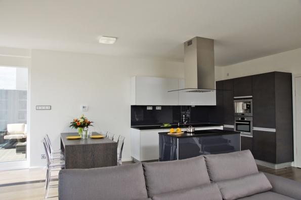 Kuchyňská linka s dýhou wengé a světlým lakem ve vysokém lesku, doplněná pracovní deskou z černé žuly, zapadá do konceptu střízlivých zemitých barev, který majitelé zvolili pro svůj dům.