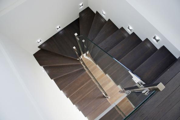 Dubové schodišťové stupně jsou mořeny do stejného odstínu jako podlaha v obývacím pokoji.