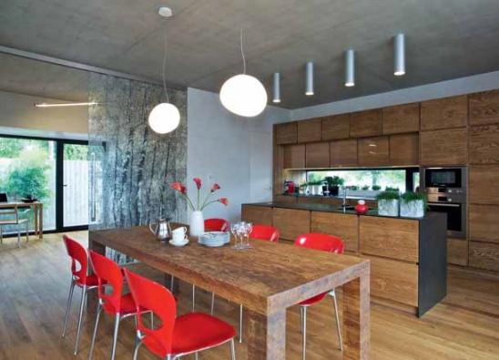 V interiéru domu, který navrhl ateliér OK Plan, architekti sjednotili dubové podlahy a nábytek a navrhli kontrastní hliníková okna (Schüco) a atypické skleněné dveře.