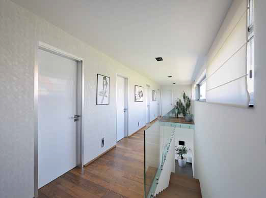 Dveře z bílého skla s hliníkovými zárubněmi charakterizují high-tech styl.